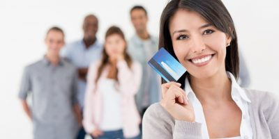 Happy business woman holding a credit card with a group of people at the background